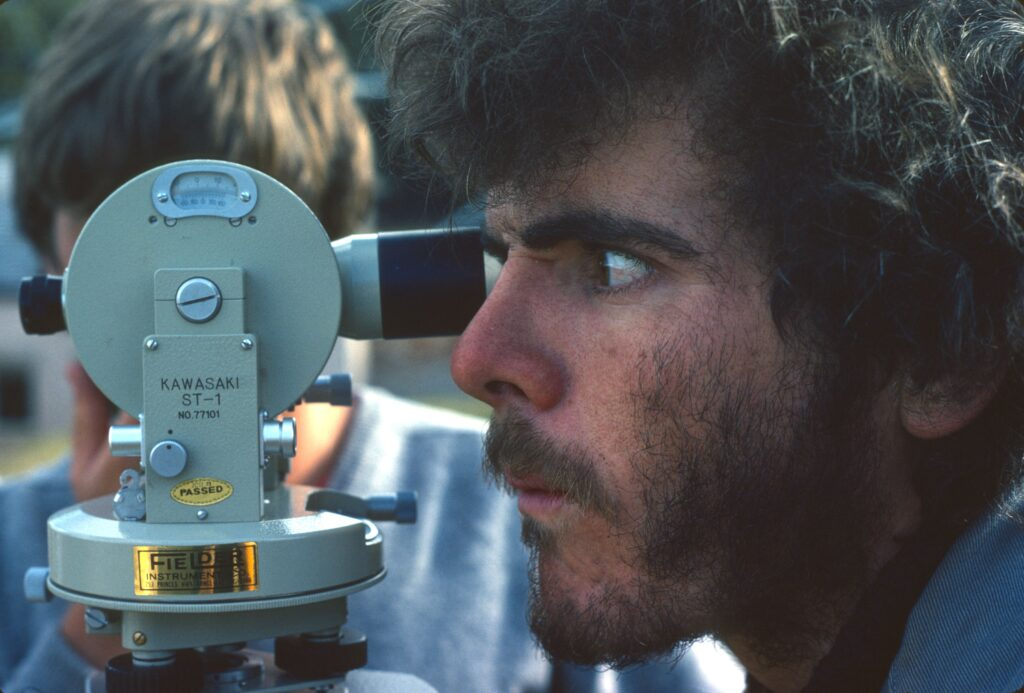 Martin Davies looking to the left through a 'dumpy' level, in 1982, courtesy of Port Arthur Historic Site Management Authority.